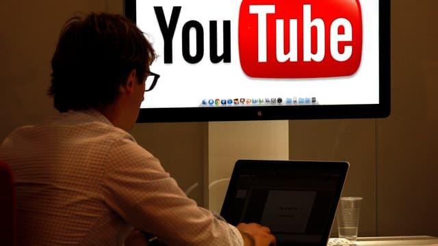 Ein Besucher sitzt an der Fernsehmesse Mipcom in Cannes vor einem Fernseher mit YouTube-Logo.