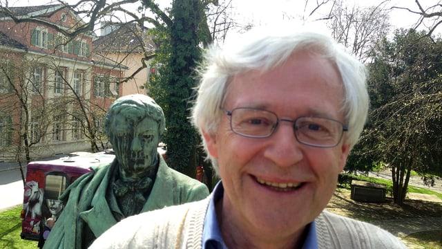 Portrait von Werner Ort, der vor der Statue von Heinrich Zschokke posiert.