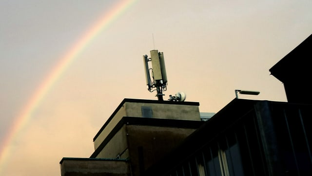 Handyantenne auf einem Dach und Regenbogen.