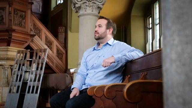 Renato Pfeffer sitzt in einer Kirche. Er trägt ein blaues Hemd.