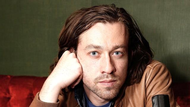 Simon Stone blickt in die Kamera, den Kopf aufgestützt auf die rechte Hand. Er trägt eine braune Lederjacke.
