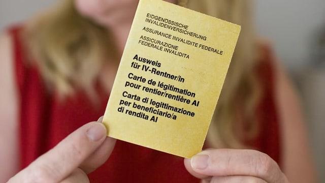 Person hält einen IV-Ausweis in den Händen.
