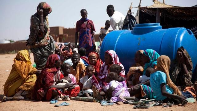 Erwachsene und Kinder sitzen um einen Wassertank.