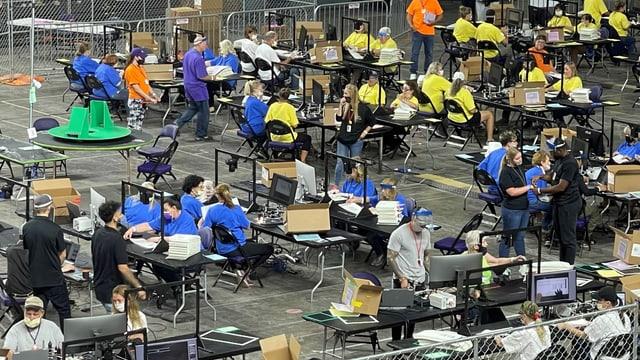 Tische mit Menschen in verschiedenfarbigen T-Shirts, die Wahlzettel zählen und untersuchen