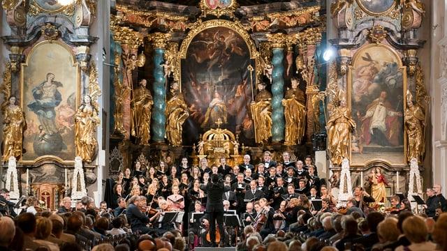 Ein Orchester spielt vor Publikum in einer prunkvollen Kirche.
