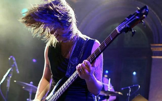 Beatrice Bass mit einer Bassgitarre und wehendem Haar an einem Aufritt.