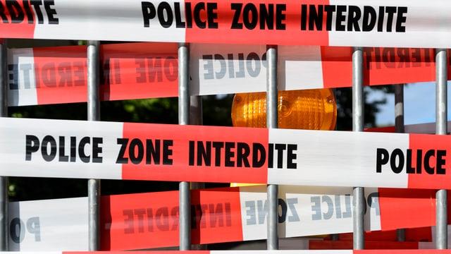 """Eisengitter und Absperrbänder mit der Aufschrift """"Police Zone Interdite""""."""