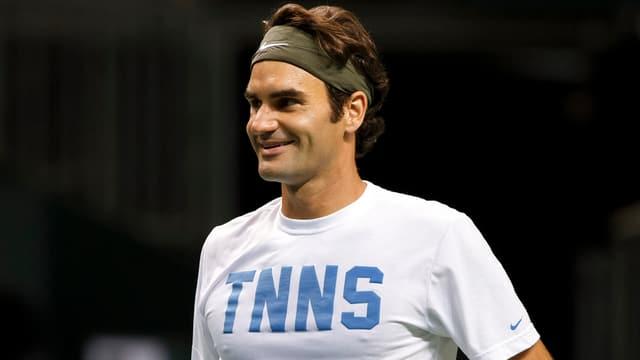 Roger Federer steht bei den Davis-Cup-Vorbereitungen lächelnd auf dem Court.