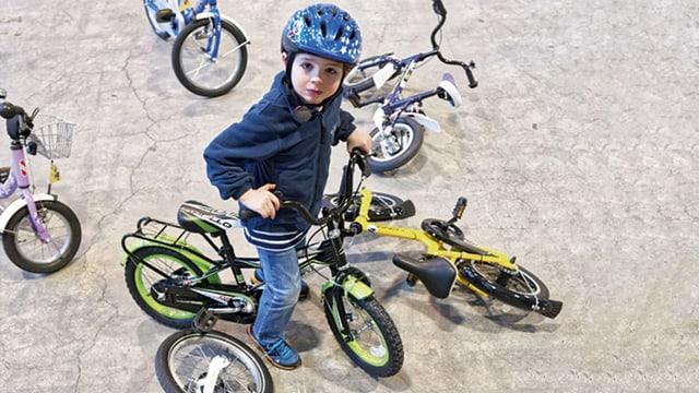 Kleiner Junge auf einem grünen Kindervelo.