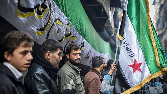 Personen stehen unter syrischer Fahne.