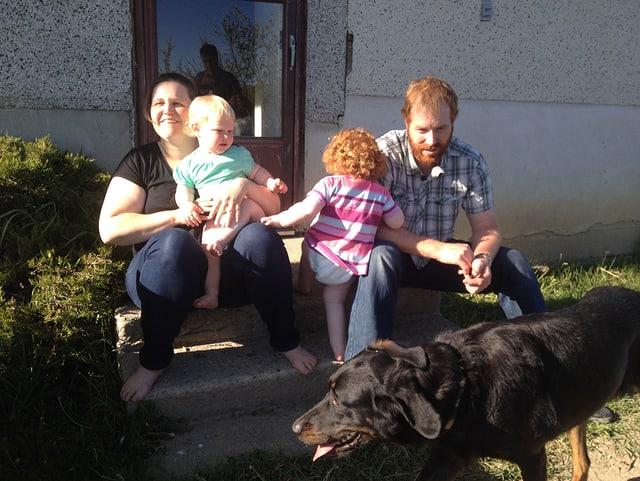 Eine Familie mit zwei Kindern und einem Kind sitzt vor dem Haus in der Sonne.