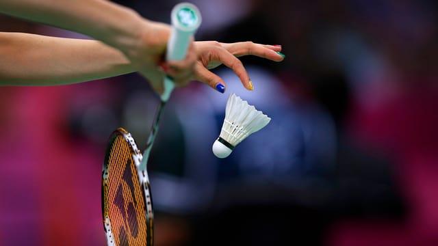 Eine Frauenhand mit einem Badminton und einem Schläger in Nahaufnahme