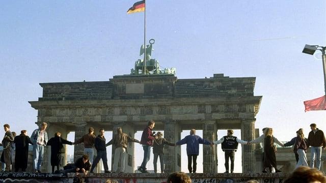 Menschen stehen auf der Mauer und halten sich an den Händen.