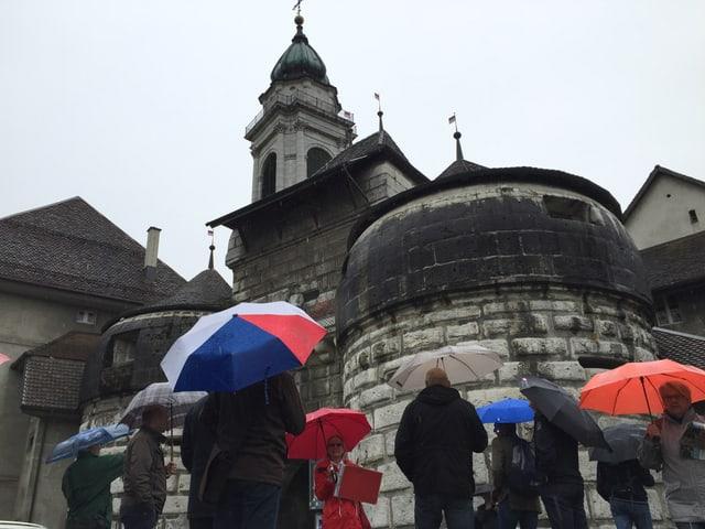 Touristen mit Regenschirmen blicken zum historischen Baseltor, dahinter eine Kathedrale