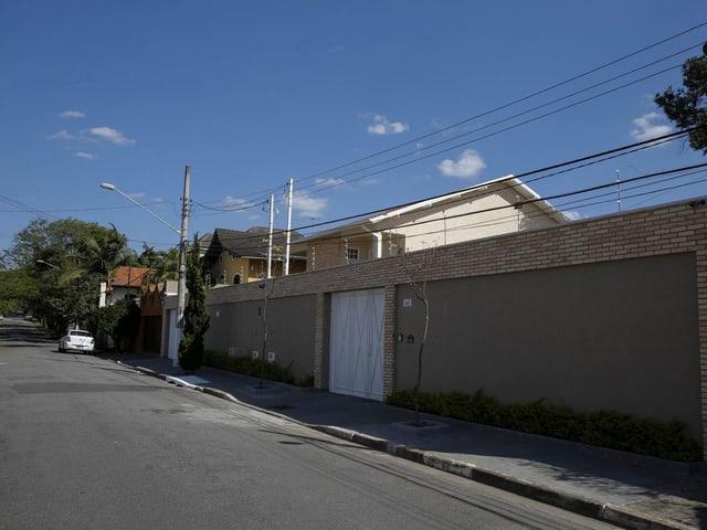 Eine Einfahrt in Sao Paulo. Hohe Mauern umgeben das weisse Haus.