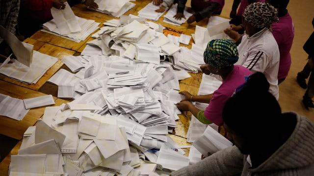 Menschen mit einem Haufen Stimmzettel auf einem Tisch.