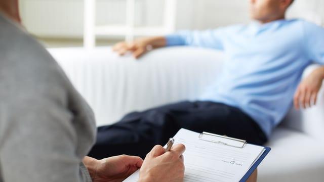 Person mit Schreibblock berät Person auf Sofa.
