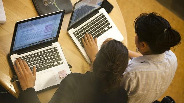 Zwei Frauen sitzen an einem Schreibtisch vor ihren Laptops.