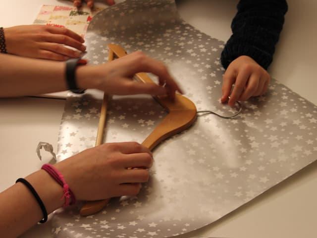 Kleiderbügel auf dreieckförmigem Geschenkpapier
