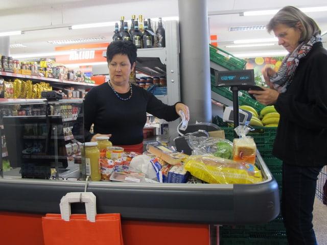 Frau an Kasse gibt einer Kundin den Kassenbeleg