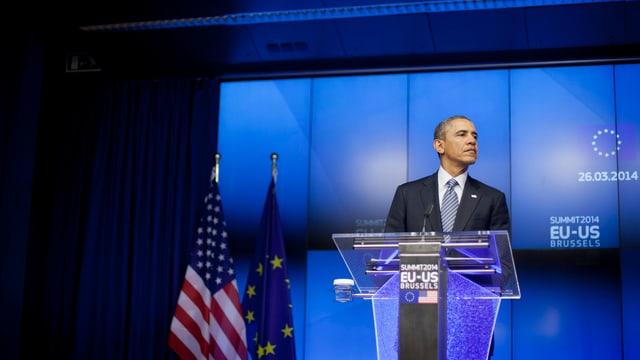 Obama an einem Rednerpult, hinter ihm EU- und US-Flagge.