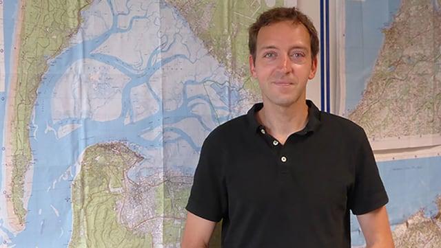 Ein Mann steht vor einer Karte