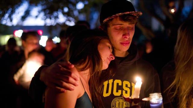 Zwei Teenager, die eine Kerze halten und sich umarmen