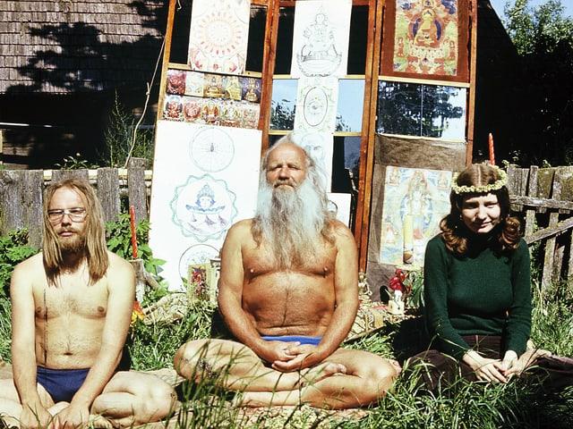 Zwei halbnackte Männer und eine Frau sitzen im Schneidersitz im Garten.