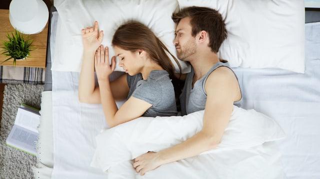 Ein mann kuschelt sich seitlich an eine Frau im Bett.