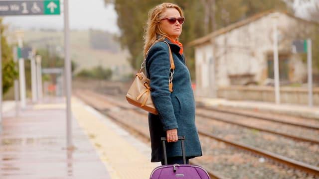 Frau steht mit Rollkoffer auf Zugsteig