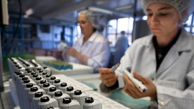 Zwei Ypsomed-Mitarbeiter bauen Injektions-Systeme zusammen.