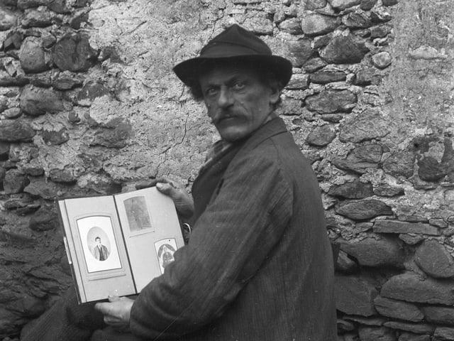 Ein Mann mit Hut und einem aufgeschlagenen Buch in der Hand.
