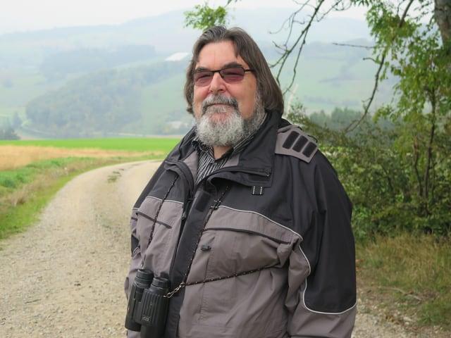 Ein Mann Brille und Bart steht vor nebligem Hintergrund