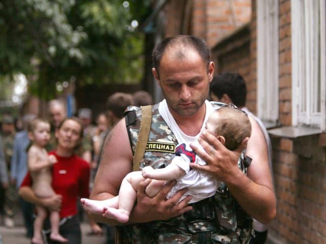 Ein Mann in Uniform trägt ein Baby