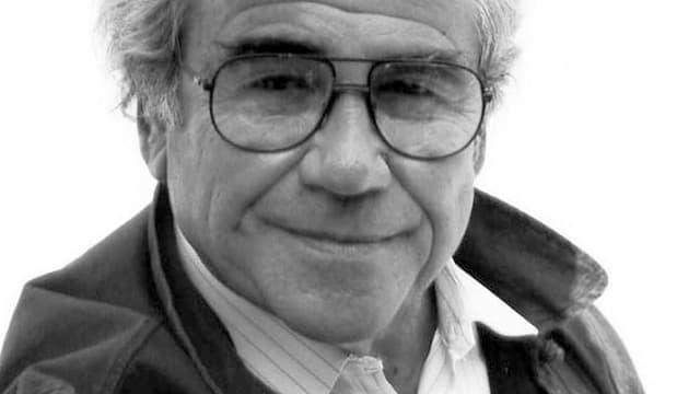 Ein älterer Herr mit Brille, lächelnd.