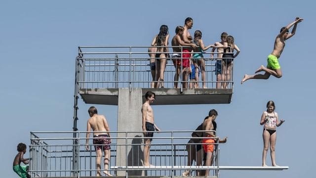 Menschen auf dem Springturm im See