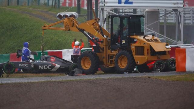 Ein gelber Kran hebt einen F1-Wagen mit dem Kran in die Höhe, unter seinem Heck sind Teile eines demolierten weiteren Fahrzeuges.