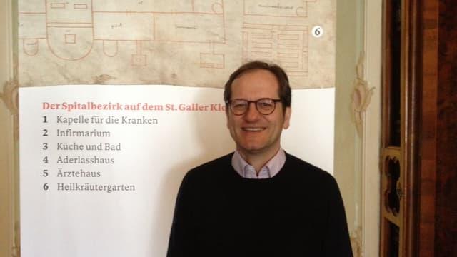 Stiftsbibliothekar Cornel Dora vor dem  St. Galler Klosterplan einem wichtigen Zeugen der Spitalgeschichte.