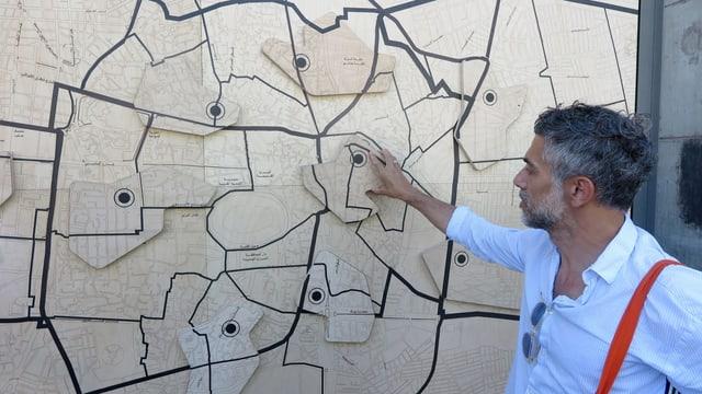Ein Mann steht vor einer grossen Wandkarte.