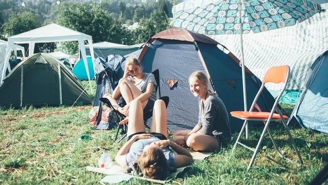 Freundinnen sitzen vor ihrem Zelt