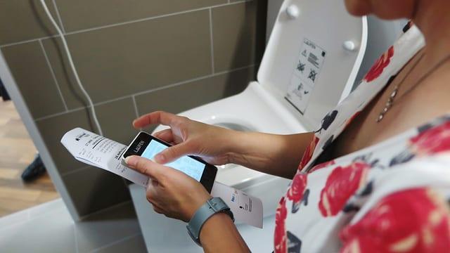 Eine Frau programmiert per App die Toilette.