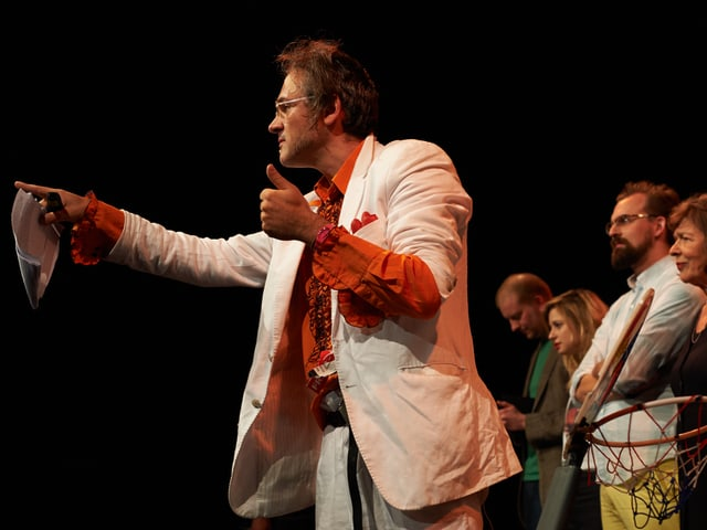 ein Mann steht auf einer dunkel beleuchteten Bühne und zeigt ins Publikum.