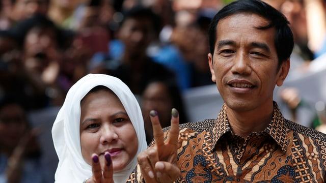 Joko Widodo (rechts) mit seiner Frau Iriana, beide zeigen das Victory-Zeichen