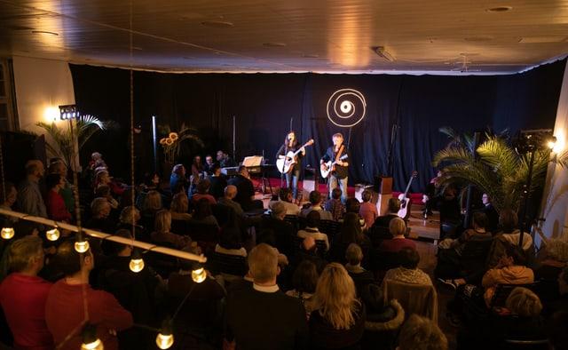 Ein Theatesaal in einer Landbeiz - Publikum im Saal, zwei Künstler mit Gitarre auf der Bühne.