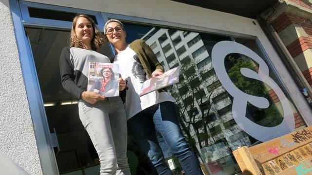 Blick von unten auf zwei Frauen mit je einem Surprise-Heft in der Hand