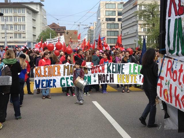Kinder und Jugendliche in roten Pullovern hinter einem bunten Banner.