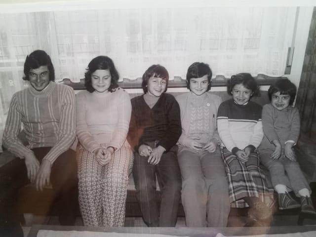 Drei Buben und drei Mädchen sitzen nebeneinander auf einem Sofa.