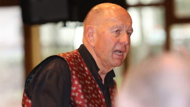 Der Mann trägt ein schwarzes Hemd und ein rot-weiss gemustertes Gilet aus Seide.