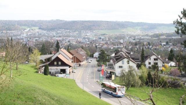 Blick von oben auf Bergdietikon, Bus fährt auf Strasse.