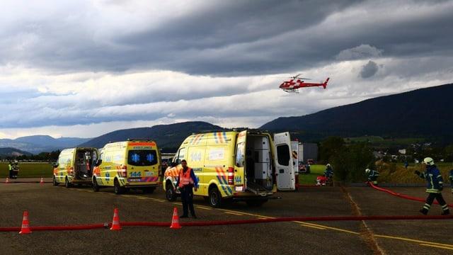 Ambulanzen stehen auf dem Rollfeld, im Hintergrund fliegt ein Rega-Helikopter